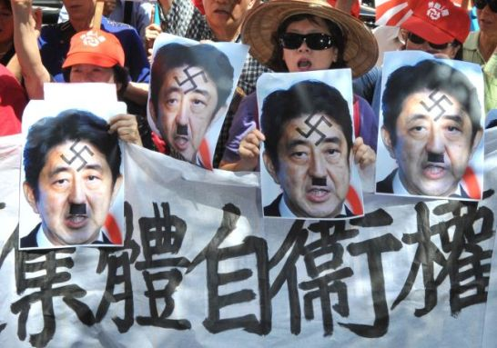 "Protesters chant slogans, display Japanese military flags and portraits of Prime Minister Shinzo Abe and a protest sign read like ""Don't forget Marco Polo Incident, Maintain peace in Asia"" during a demonstration in front of Japan's de facto embassy in Taipei on July 7, 2014. Dozens of slogan-chanting protesters from Taiwan's Labour Party and a pro-unification group protested Japan's controversial shift for its Pacifist stance allowing it to go into battle in defence of allies. AFP PHOTO / Mandy CHENG../2014-07-07 15:27:06/"